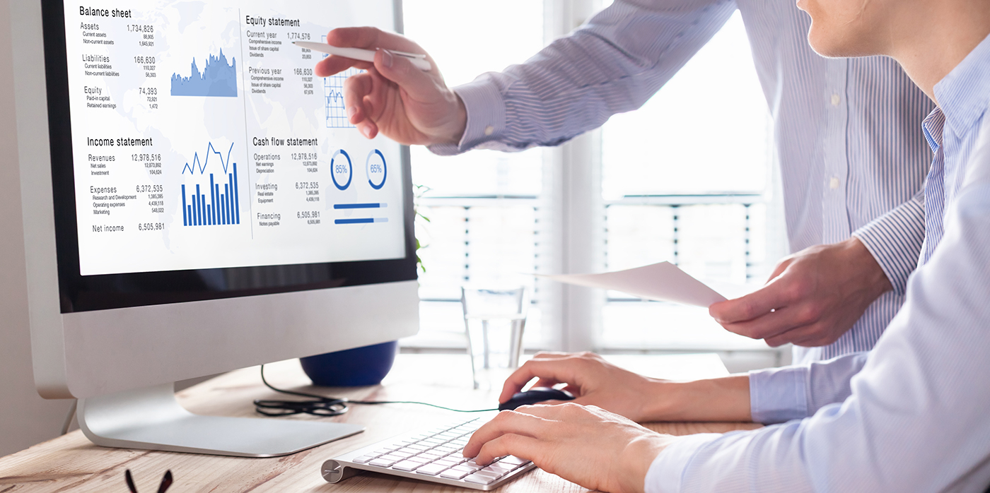 Two people in office environment reviewing financial report on computer screen