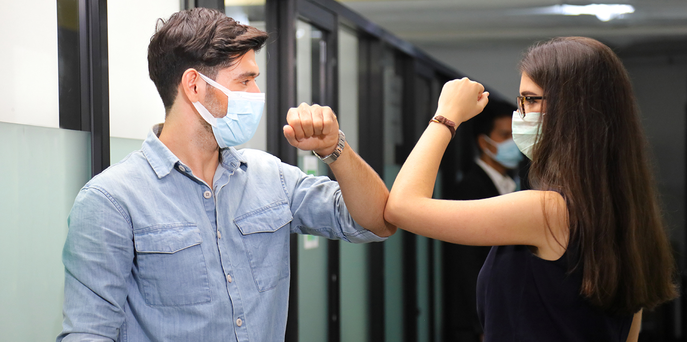 Two people elbow bumping in office corridor