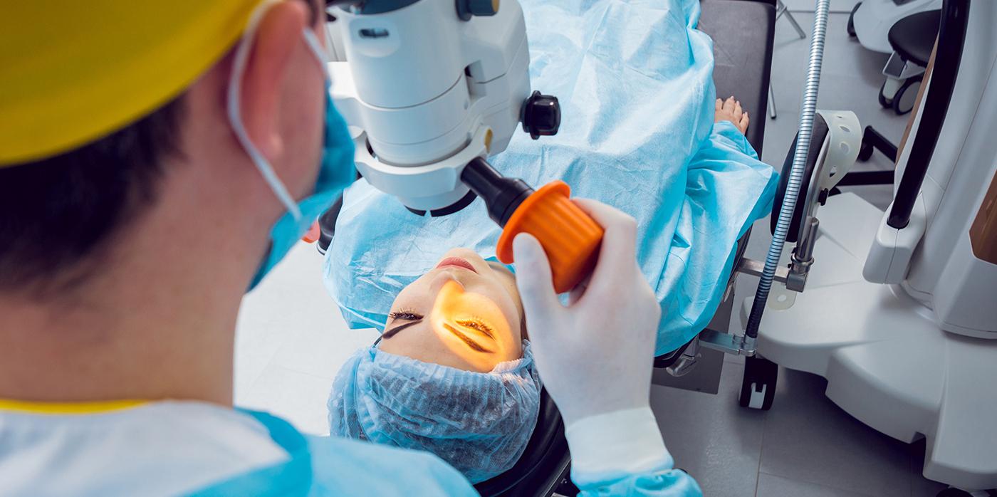 lab technician looking down microscope