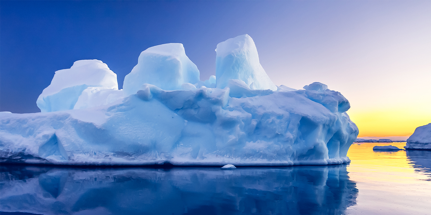 Imageof an iceberg surrounded by blue sea and a sunset
